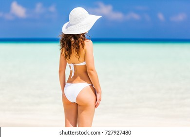 Back of young woman in bikini standing on the beach