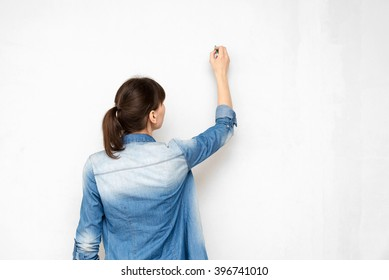 back of young woman in casual clothes with pencil drawing or writing on empty wall
