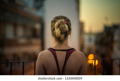 Back of a young woman looking at the cityscape from a terrace at sunset