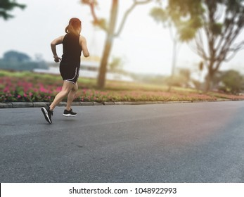 Back of young woman runner running on the road in the park with sunshine morning, copy space