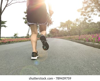 Back of young woman running on the road in the park with sunshine morning, lens flare. copy space