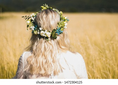 Back of the young woman in a white dress in boho style with a floral wreath in the summer in the field.
