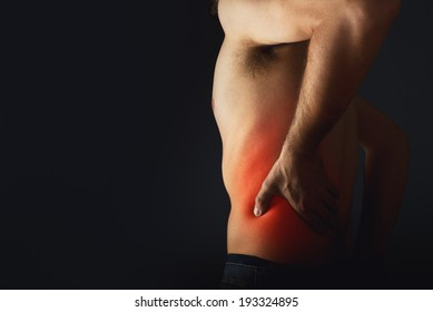 Backache. Pain in the lower back. Shirtless man touching his back for the pain.