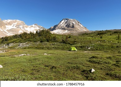 Backcountry Camping Tent in Alpine Meadow and Distant Rocky Mountain Peaks Nature Landscape, White Goat Wilderness Area, Alberta Canada