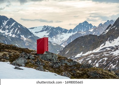 A backcountry ski hut outhouse in the Talkeetna Mountains of Alaska. Snow still covers most the area in July.