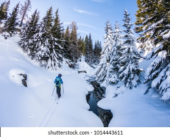 Backcountry ski touring in the fresh snow Young woman touring on skis in sunny winter day. Girl advances on touring skis across white snow forest and frozen river. Skier in powder snow on a sunny day.