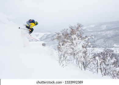Backcountry skier jumps off a cornice near the summit of a small peak in backcountry Hokkaido, Japan. Yellow jacket, blue backpack powder skiing in Japan. Dropping off a cornice extreme skiing.