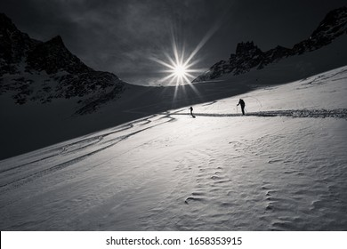 Backcountry Skiers Ascending Steep Slope In Austrian Alps, Black and White