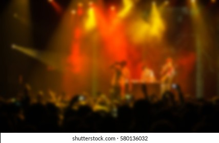 Backdrop of big hip hop concert of in night club.Bright yellow & red stage lighting,crowded dancefloor with music fans enjoy the show.Blurred background to place text.Music festival blurry background