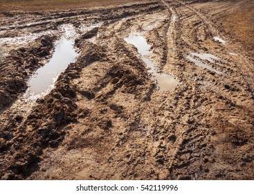 Backdrop of thick viscous slippery tracks from tires on clay off-road in provincial village sunny spring evening after rain with place for text on gray surface