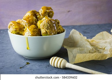 Backed cauliflower with honey soy sauce served in a white bowl