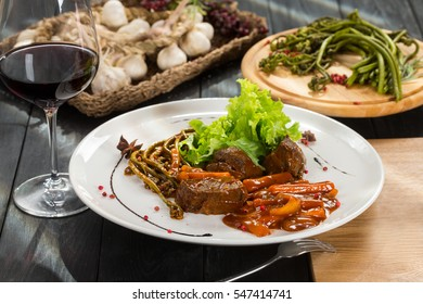 Backed red deer meat with weeds on white dish with red wine and black wooden background.