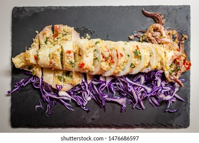 Backed squid stuffed with bread, parsil and tomato and side of red cabbage. Italian recipe.