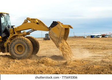 Backfilling operation on construction site, area, zone, yard with heavy loader using signalman.