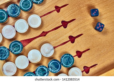 Backgammon game. Game dice made of stone lie on the backgammon board against the background of checkers. Flat lay