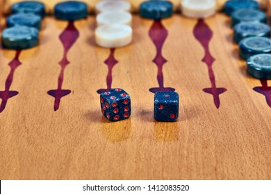 Backgammon game. Game dice made of stone lie on the backgammon board against the background of checkers. Close-up