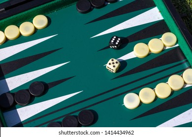 Backgammon game in starting position seen diagonally with a black six and a white five on the dice as a classic start