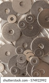 Background abstract pattern and texture of numerous overlapping stainless steel washers in an overhead full frame view