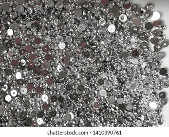 Background - abstraction, shiny metal semi-beads are on a white plate.