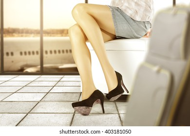 background of airport and blured suitcase with slim woman legs and black heels