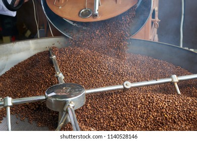 Background  of Arabica coffee beans spilling for roasting in drum machine of local artisan roastery, copy space