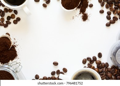 Background with assorted coffee: cups of espresso, coffee beans, powder and capsules on white background. Space for copy. Top view. Flat lay