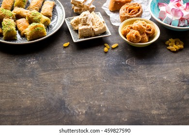 Background with assorted traditional eastern desserts. Different Arabian sweets on wooden table. Baklava, halva, rahat lokum, sherbet, nuts, dates, raisins, kadayif in colorful plates. Selective focus