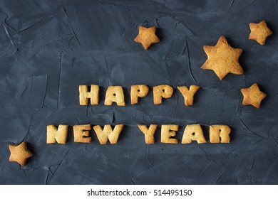 background with baked gingerbread stars and words happy new year on the concrete background. creative idea