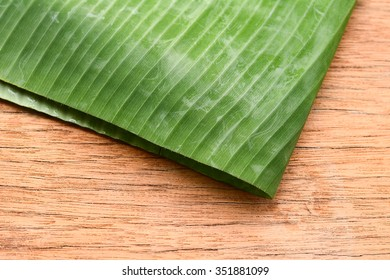 Background banana leaves on the wooden floor.