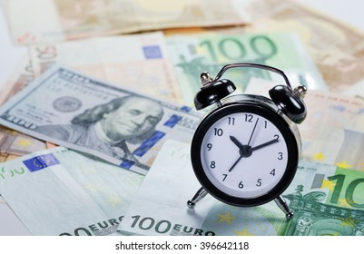 Background with banknotes. Selective focus used on the clock