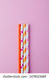 Background for a banner with eco-friendly paper colorful straws or  cocktail tubes for the holiday on pastel pink background top view with copy space.reusable biodegradable materials concept flat lay