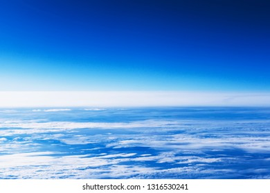 Background of beautiful fluffy natural white clouds texture with blue sunset sky shoot from window of airplane flight fly above with top view cloudscape. Present freedom holiday travel journey
