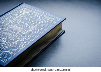 Background with beautiful hardcover blue gold book, moody style toned, copy space, negative space, top view. selective focus.