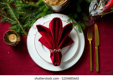 Background of beautiful served table with candles, Red tablecloth and napkins, white china, gold cutlery, crystal champagne glasses, spruce tree branches. Top view. Holiday setting, Christmas mood.