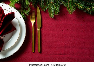 Background of beautiful served table with Red tablecloth and napkins, white china, gold cutlery, spruce tree branches. Top view. Holiday setting, Christmas mood.