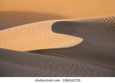 Background with beautiful structures of sandy dunes at sunrise in the Sahara desert
