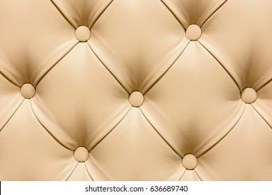 Background of beige leather quilted in the form of rhombuses