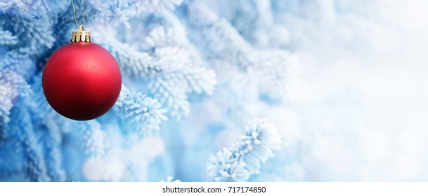 Background of Big Red Christmas Ball on the Christmas Tree with Snow in the Frozen Winter Day