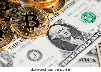 Background with Bitcoin cryptocurrency coins on one US Dollar. Virtual cryptocurrency concept. Bitcoin BTC cryptocurrency coins and banknotes of one US Dollar. BTC vs USD