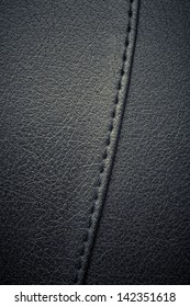 A background of black stitched leather.