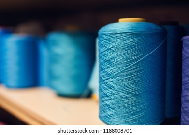 Background with a lot of blue coils with threads. Bobbins are stacked in a rows, one on the other. Selective focus