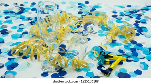 Background of blue confetti, yellow streamers and champagne glasseson white background