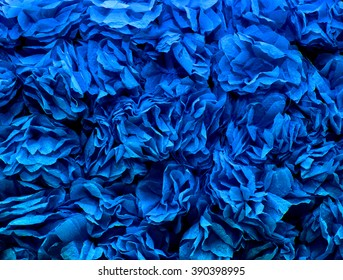 background of blue flowers made of crepe paper. pleated paper decorations closeup, texture