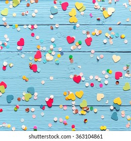 Background of blue painted wooden wall with colorful pink, red, yellow and green heart and circle confetti