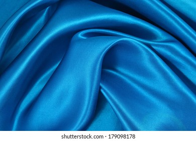 Background from a blue satin fabric with picturesque folds