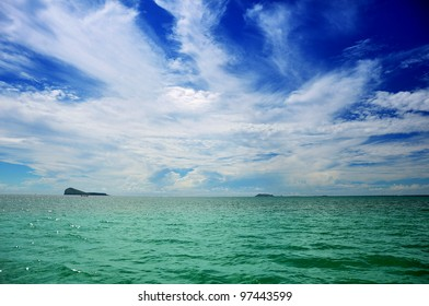 Background with Blue sky with clouds and green ocean