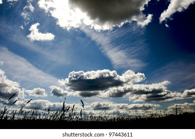 Background Blue sky with clouds and a piece of field