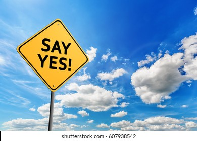 Background of blue sky with cumulus clouds and yellow road sign with text Say Yes!