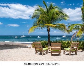 With a background of blue sky, puffy white clouds and the Pacific Ocean, including copy space, three wooden beach chairs sit under a palm tree on Playa Ocotal beach in Guanacaste, Costa Rica