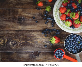 Background blueberries and strawberries in the plates. Top view